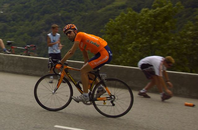 Inigo Landaluze (Euskaltel-Euskadi) contemplates the continuing climb to Courchevel, while a fan runs for his discarded bottle.