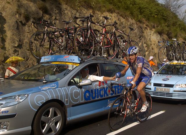 Servais Knaven (QuickStep) showing signs of a crash and getting a little help from team car.